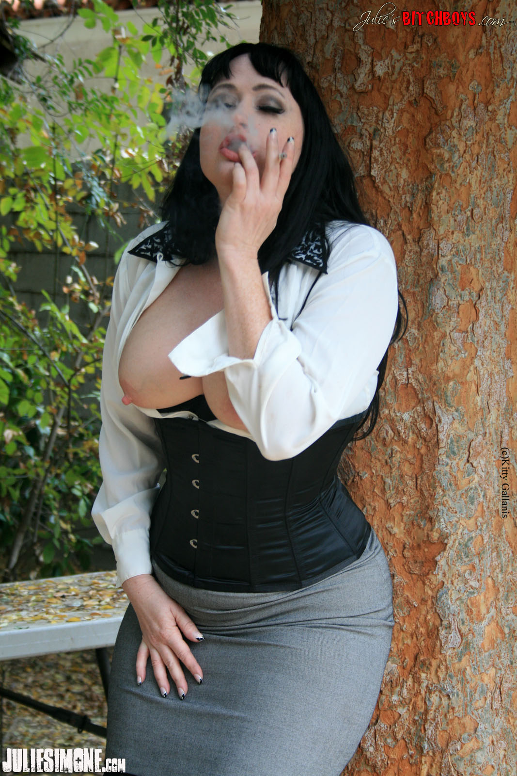 Mistress in leather smokes with strapon